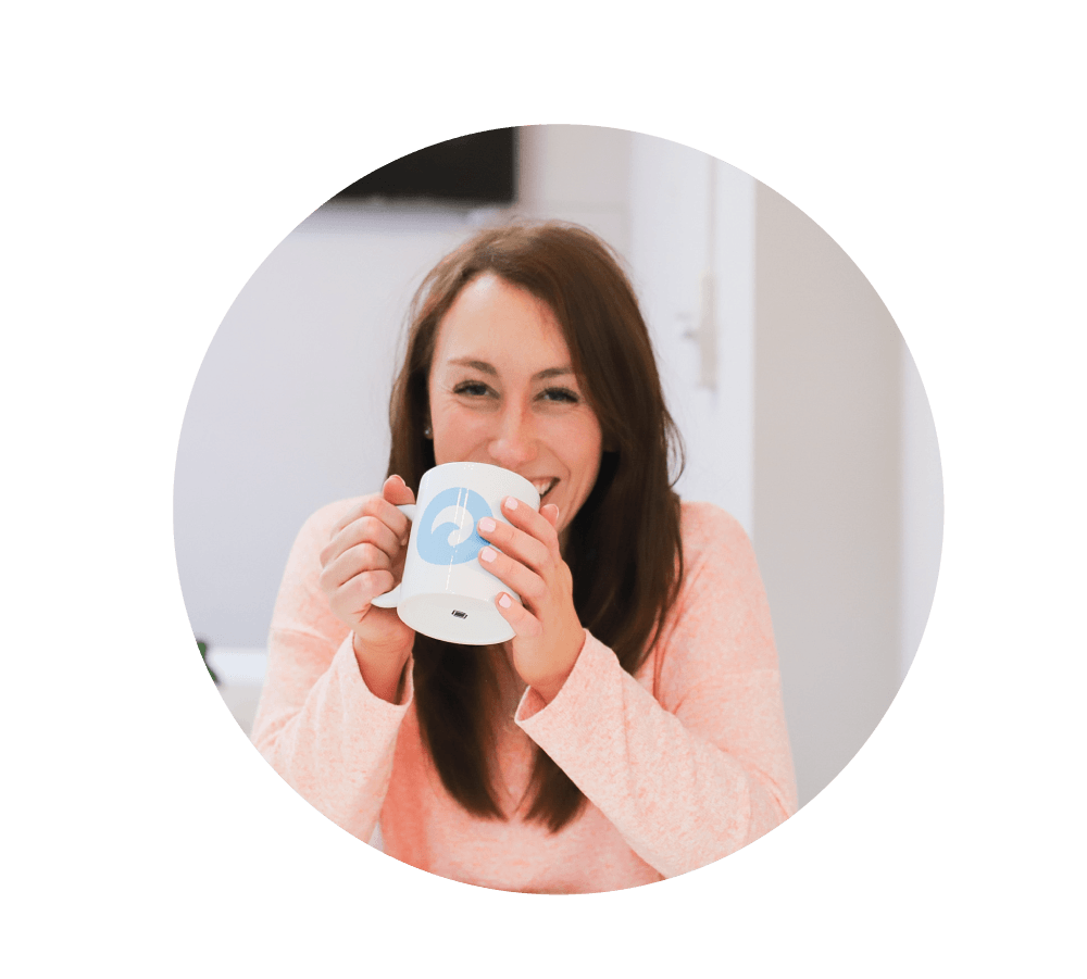 """Photo of girl with brown hair wearing a pink top, holding a white mug with the ocean digital studio logo on (which is a blue circle with a wave in the middle)."