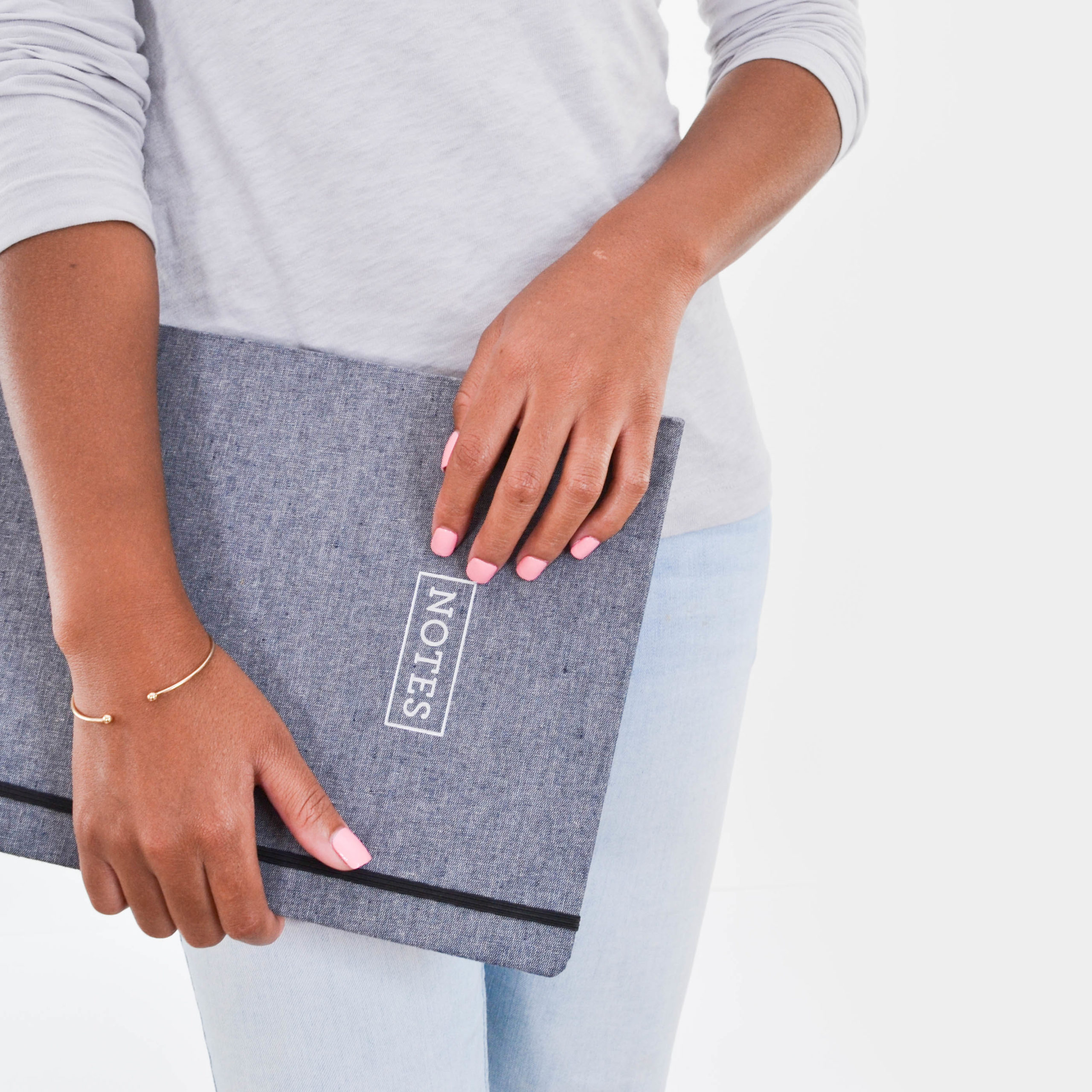Women wearing a grey top and blue trousers holding a grey 'notes' book