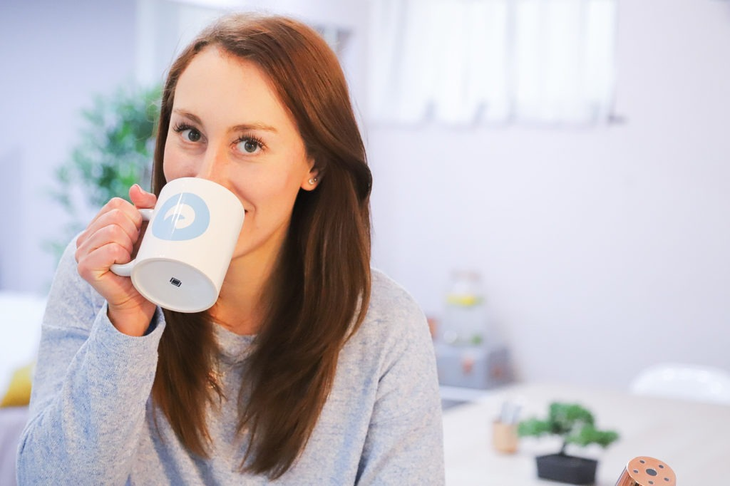 """Photo of girl with brown hair wearing a blue top, holding a white mug with the ocean digital studio logo on (which is a blue circle with a wave in the middle). """